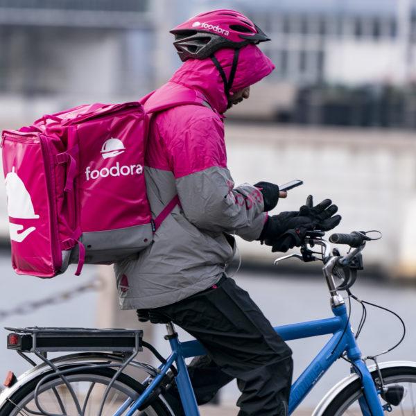 Foodora-cyklist med rosa ryggsäck cyklar och kollar på sin mobiltelefon.
