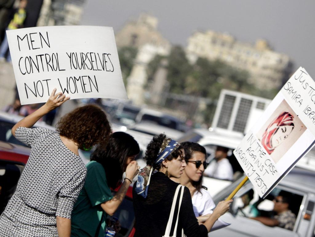 Kvinnor på en trafikerad gata håller upp plakat. Ett av dem har texten, Men control yourselves, not women.