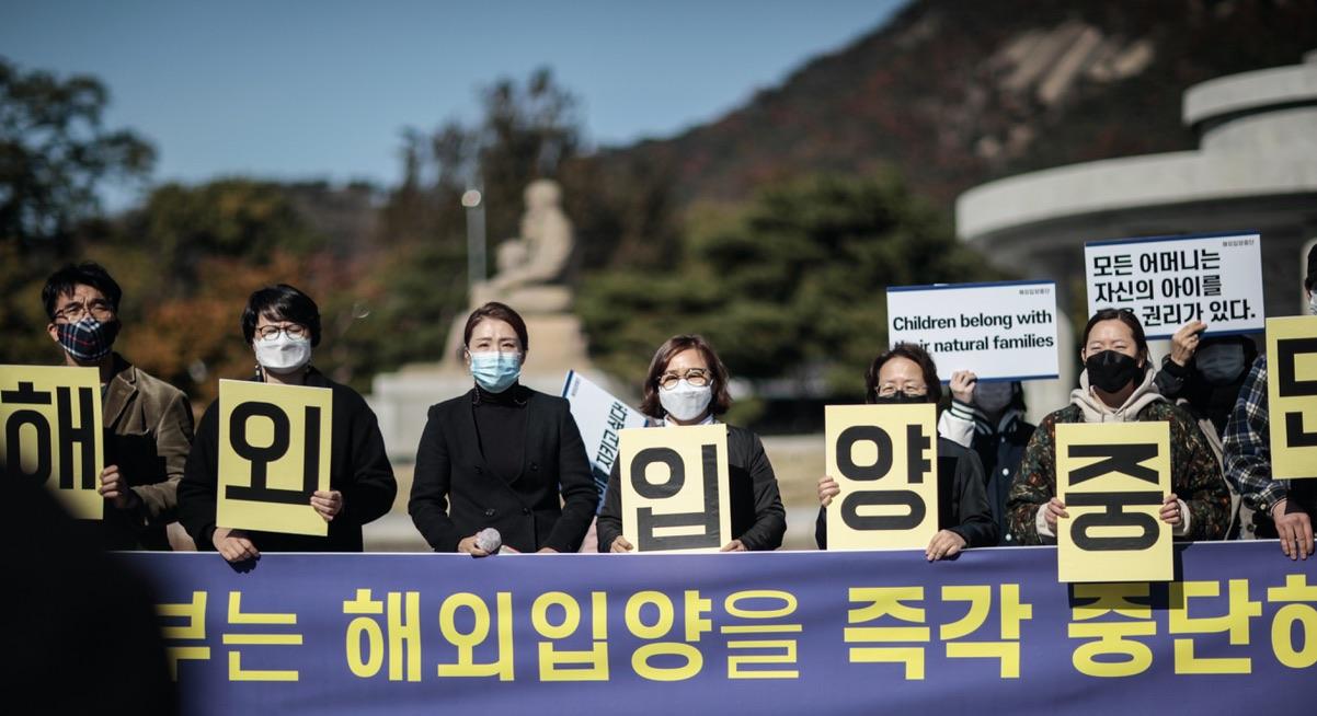 Ogifta mödrar demonstrerar mot adotionsindustrin. Framför sig har de en lila banderoll med gul text.