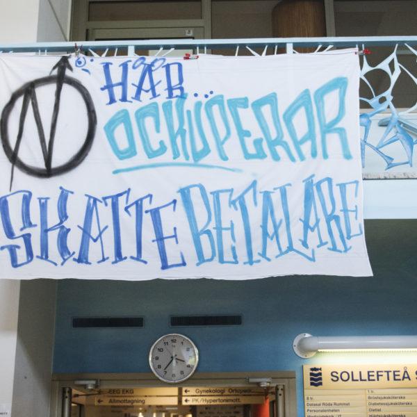 Bild på en vit banderoll med texten Här ockuperar skattebetalare.