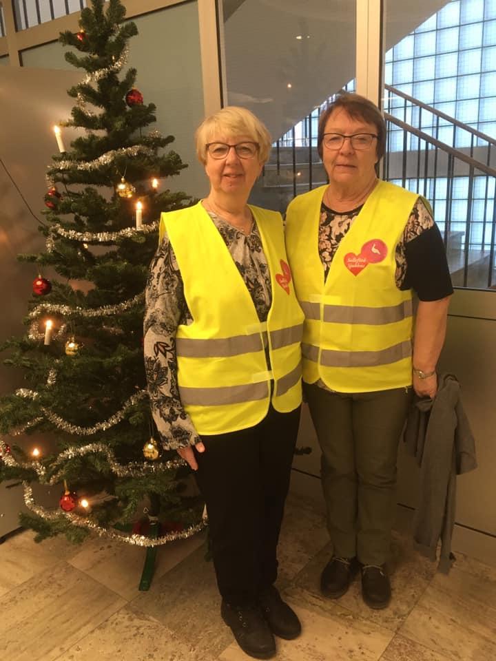 Barbro Mikaelsson tillsammans med medockupanten Anita poserar i gula västar framför en julgran.
