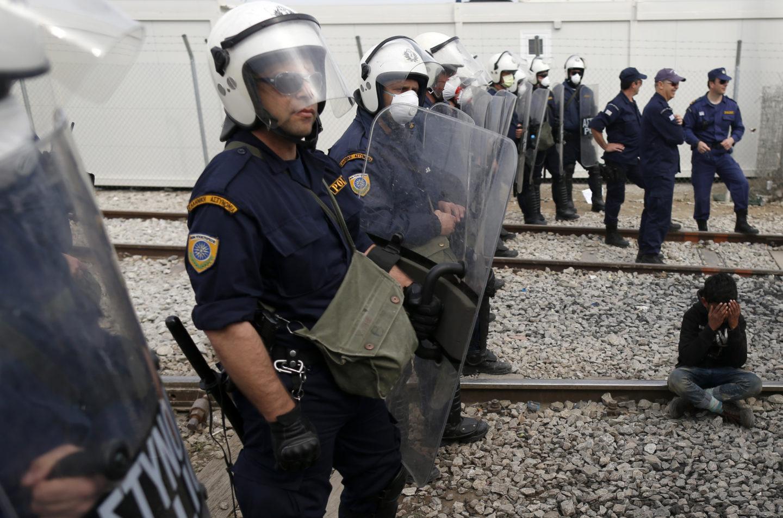 Poliser med vita hjälmar och plexiglassköldar står uppradade längs ett tågspår. En pojke sitter med nedböjt huvud framför dem.