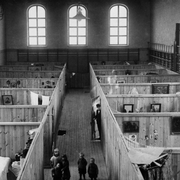 Svartvit fotografi över nödbostäder byggda i en stor sal.