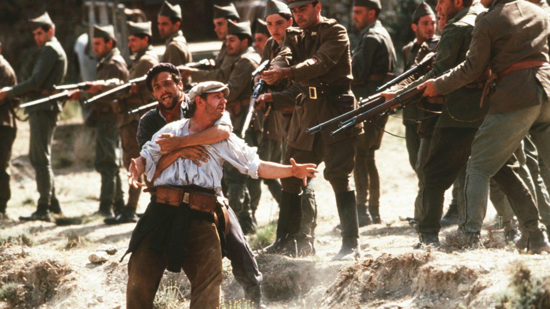 Stillbild från filmen Land och frihet. En man med sjal runt halsen håller om en man med vit skjorta. Soldater i uniformer pekar sina gevär mot dem.