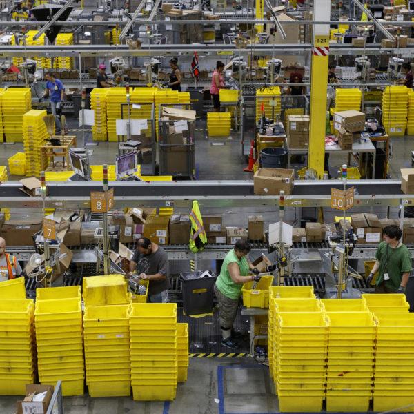 Översiktsbild över ett lager där arbetare står och packar varor.