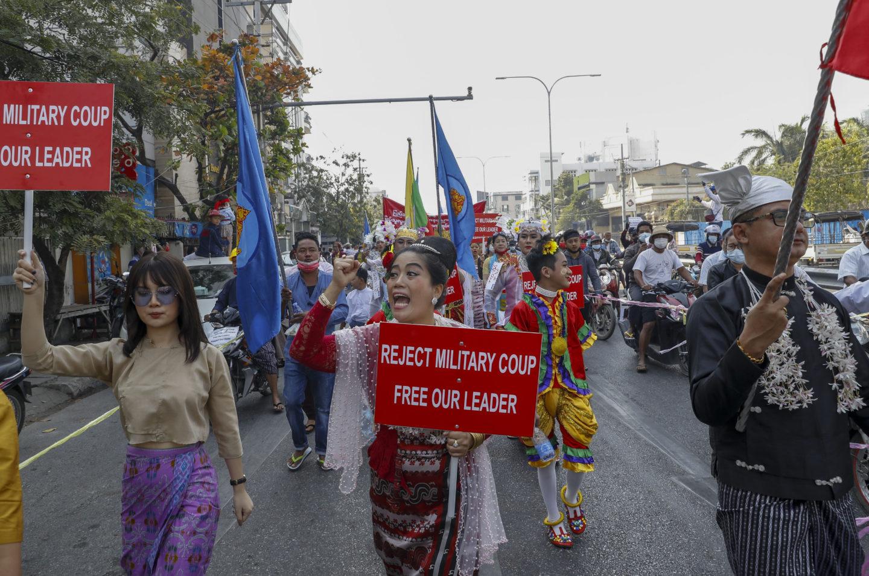 Demonstranter i Myanmar med skyltar med texten Reject military coup, free our leader.