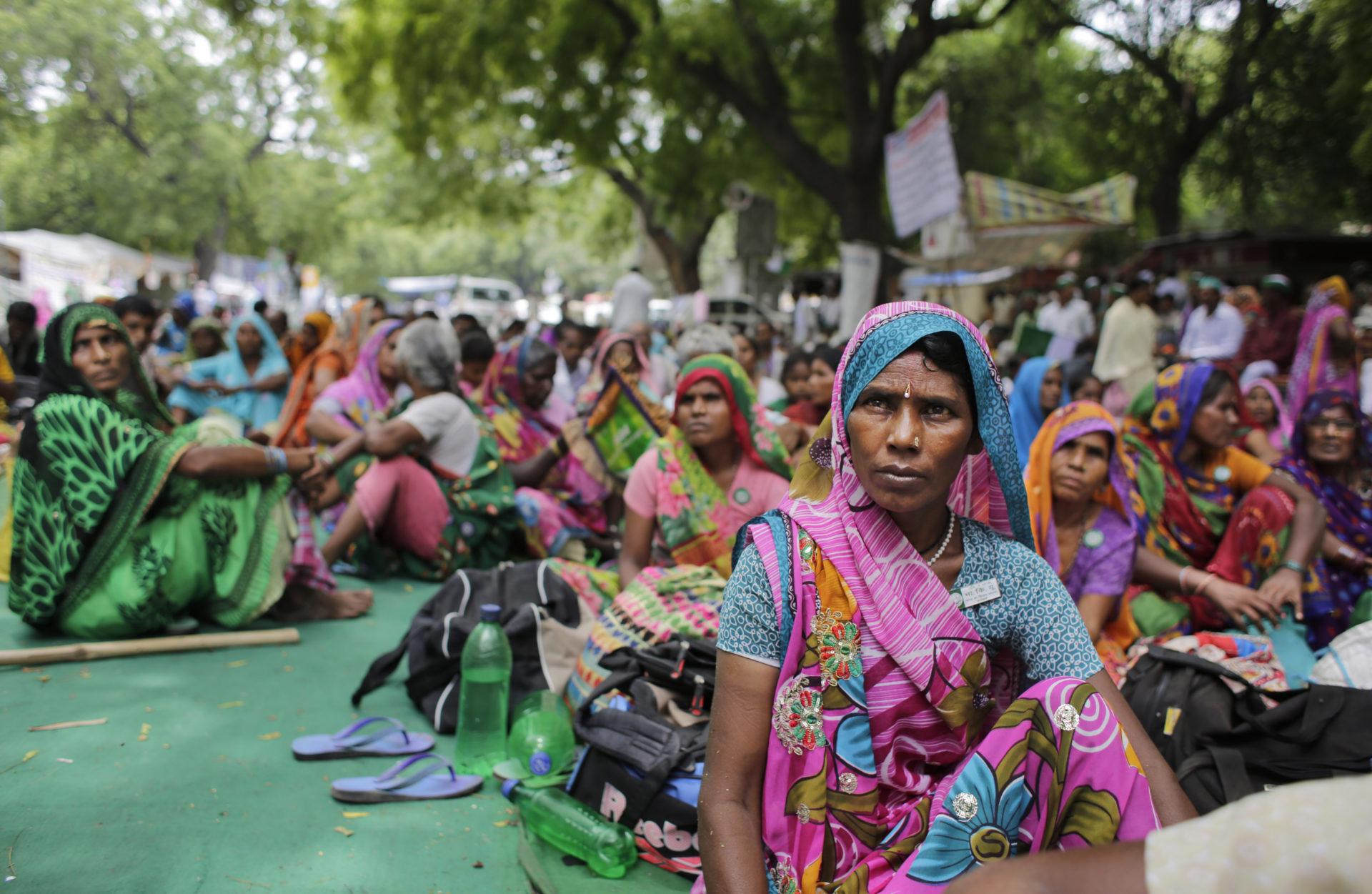 Kvinnliga bönder i färgglada saris sitter på marken i en av den senaste tidens många bondeprotester i Indien.