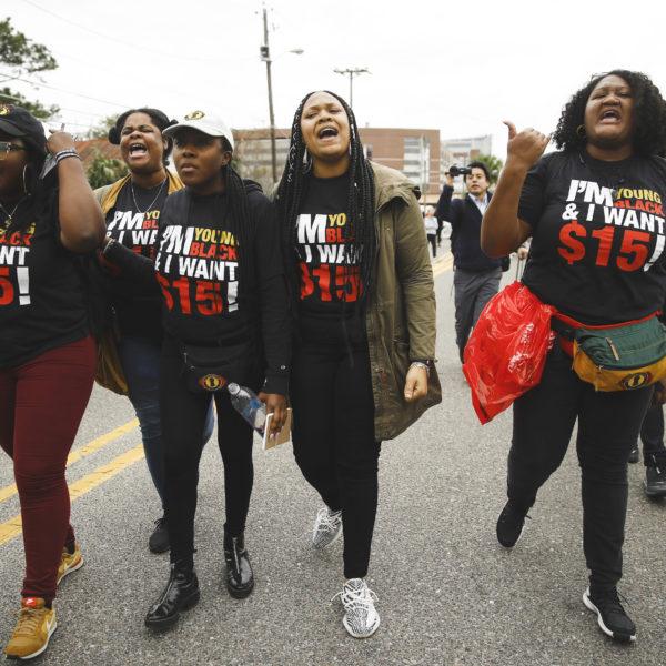 Fyra afroamerikanska kvinnor i ett demonstrationståg. På deras svarta t-shirts står det Fight for 15 med vitt och rött.