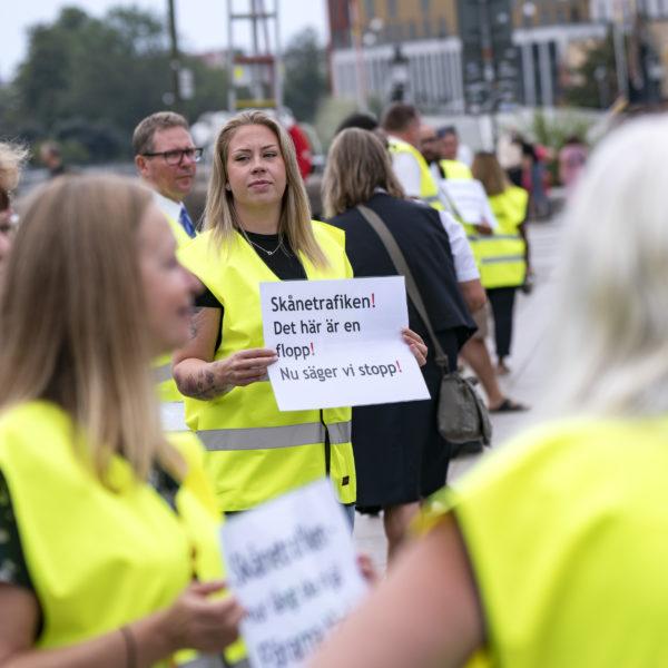 Demonstranter i gula västar och med skyltar mot Arrivas neddragningar på Pågatågen.