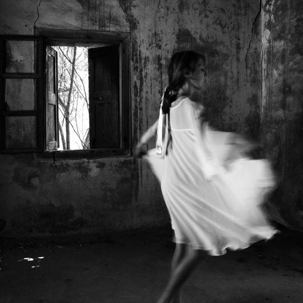 Svartvit bild där Lene Marie Fossen syns dansandes i ett avskalat rum i vit klänning.