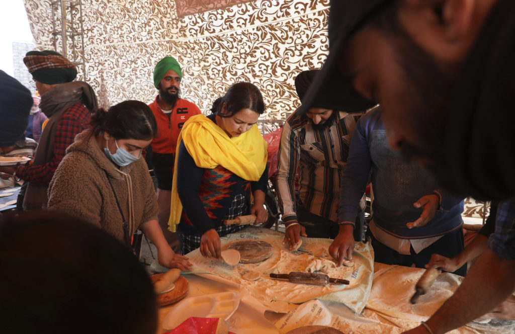Kvi9nnliga indiska bönder står runt ett bord och förbereder mat.