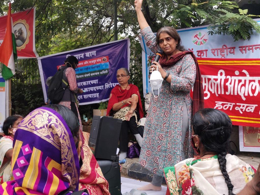 Seema står på en upphöjning, framför plakat och håller ett tal. Ena handen höjer hon i luften.