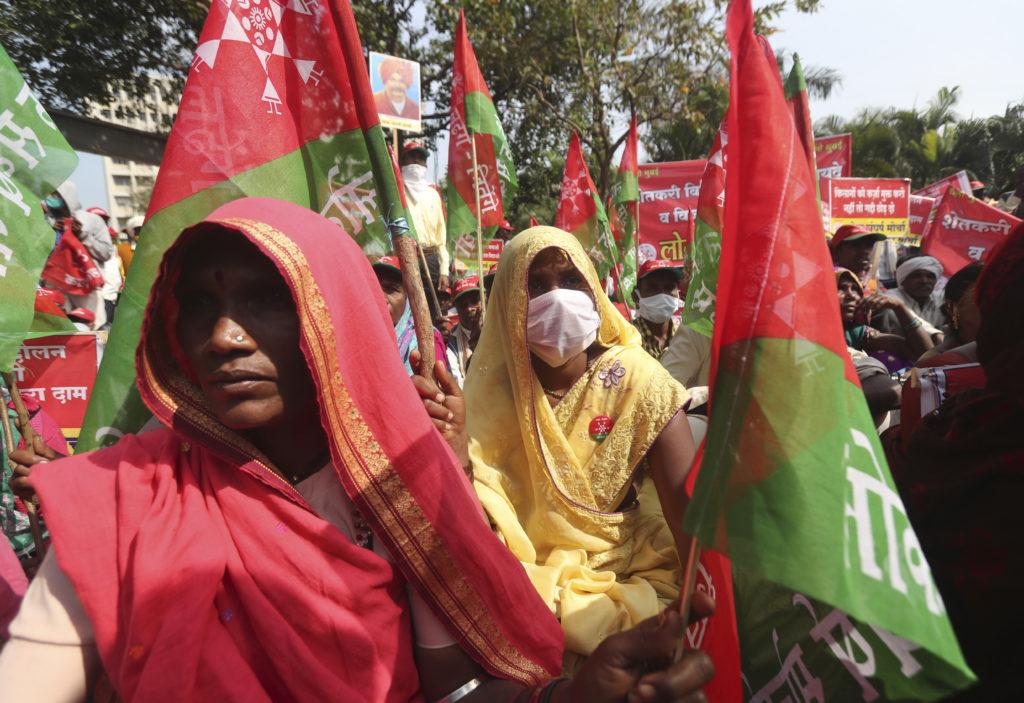 Indiska kvinnliga bönder i röda och gula saris och med röda och gröna flaggor demonstrerar.