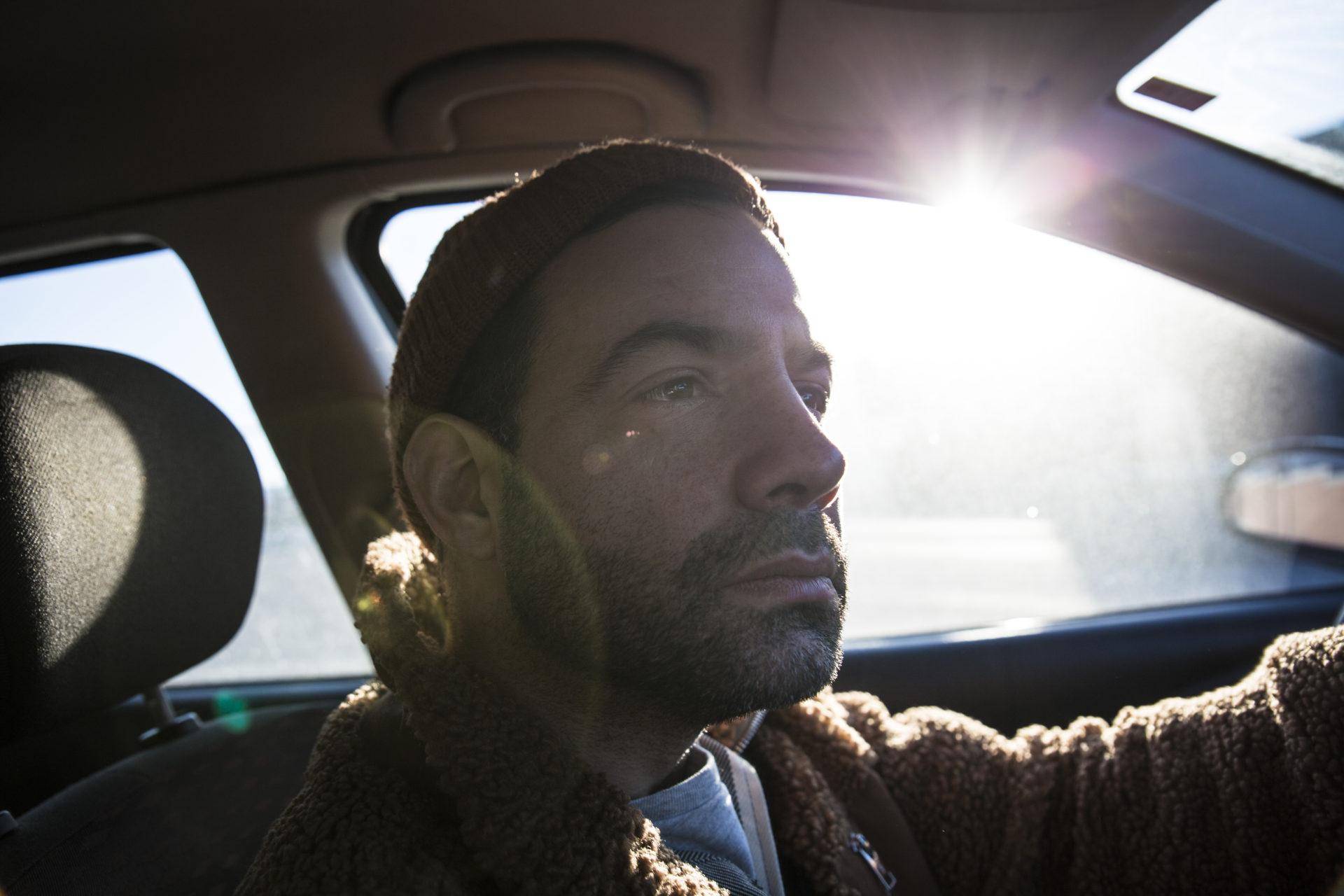Pierro Dall'Osso fotograferad bakom ratten i sin bil, från passagerarsätet. Solen lyser in i sidorutan.
