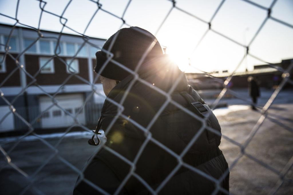 Chris, som vill vara anonym, fotograferad genom ett stängsel i ett bostadsområde.