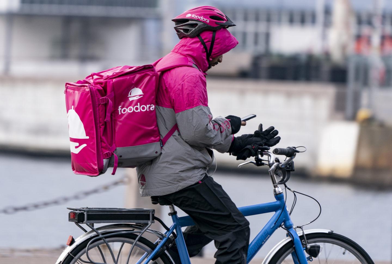 Foodora-cykelbud som kollar sin mobil.