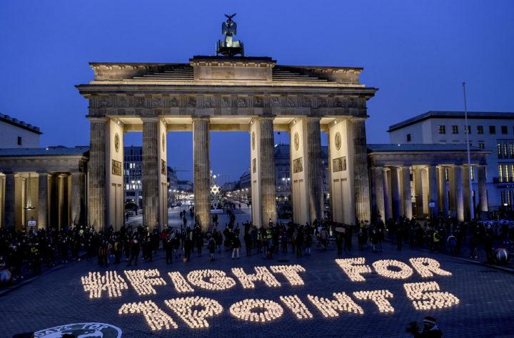 Marschaller på Brandenburger tor formerar texten Fight for 1,5.