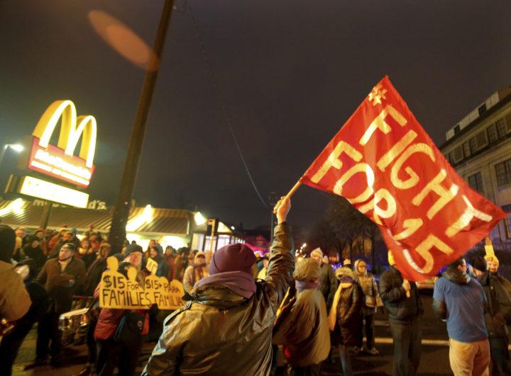 Demonstration framför ett mcdonalds. Det är kväll och mörkt och en demonstrant håller en röd flagga med texten Fight for 15. McDonalds-M:et syns i bakgrunden.