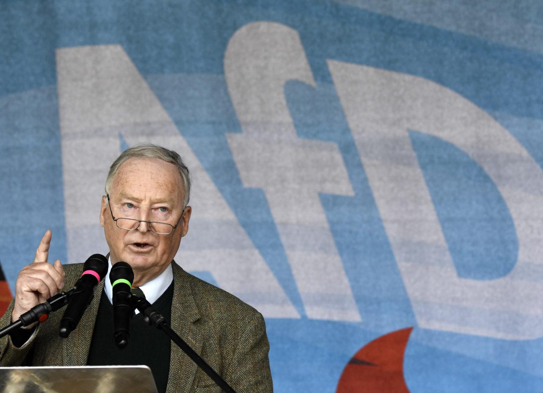 Alexander Gauland i en talarstol med ena fingret i luften. Bakom honom vajar en ljusblå flagga med texten AfD.
