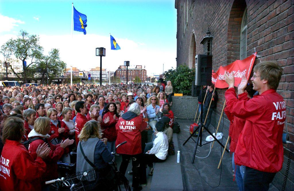 Kommunalmedlemmar i röda jackor samlade utanför stadshuset i Stockholm, under strejken 2003.