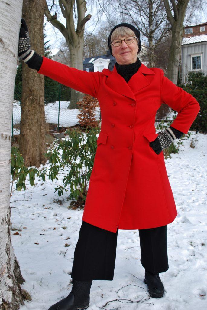 Susanne Fransson, utomhus med armen lutad mot ett träd och andra handen i sidan. Hon har en röd kappa, mössa och vantar.