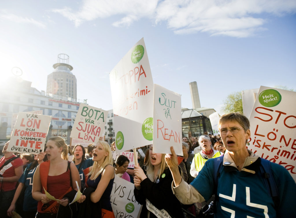 Medlemmar i Vårdförbundet demonstrerar på ett soligt Medborgarplatsen. På ett plakat står texten Slut på rean.