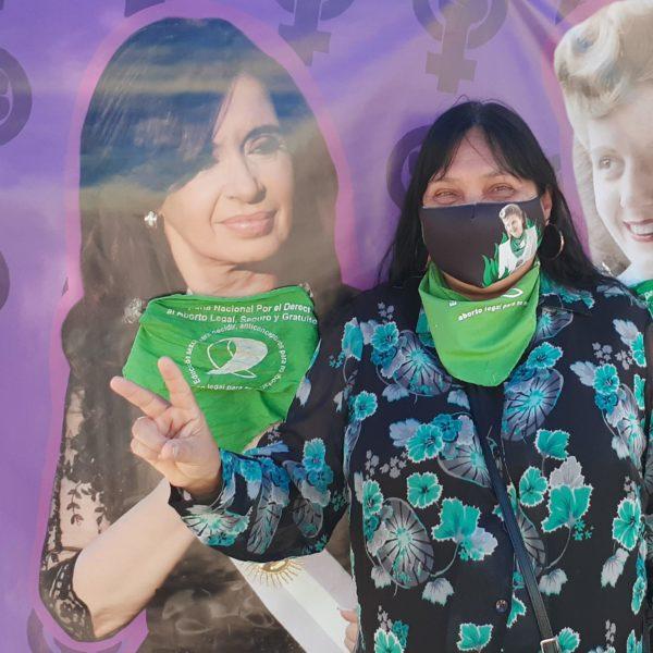 Monica Menini med grön sjal runt halsen och munskydd. Hon lyfter två fingrar i luften.