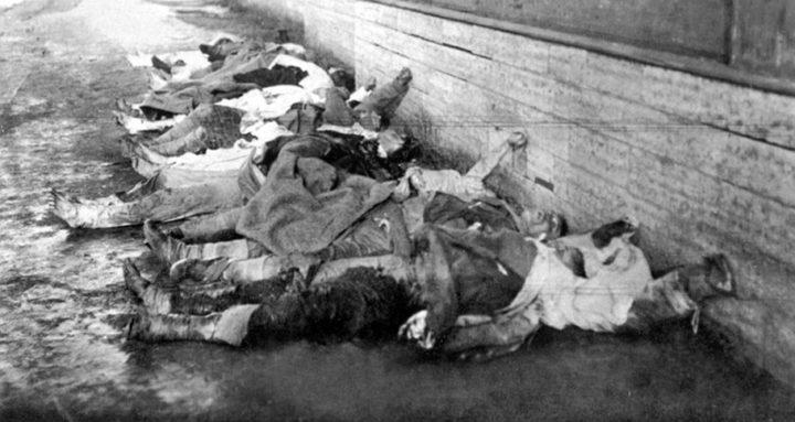 Svartvit bild över en 12 kroppar på rad längs en vägg.