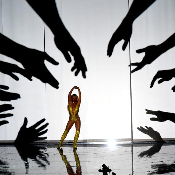 Britney Spears på en scen med stora siluetter av händer som sträcker sig mot henne.