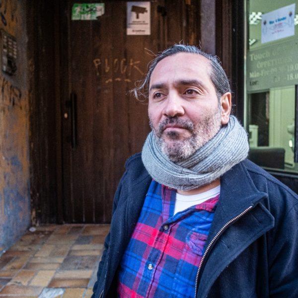 Nicolas fotograferad framför hyreshusets port, som är täckt av klotter.