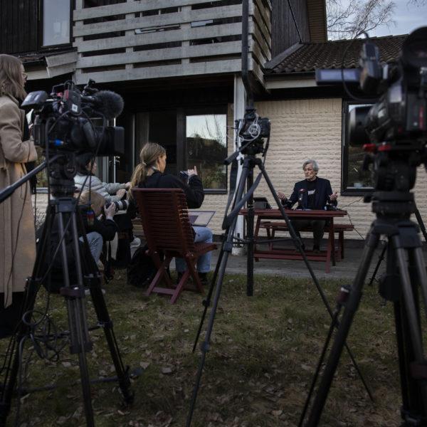 Göran Lambertz i sin trädgård framför ett uppbåd av kameror och reportrar.