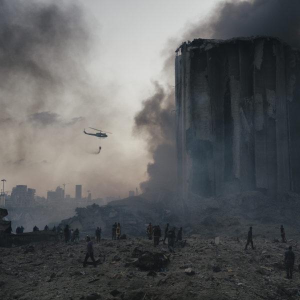 En brandsläckarhelikopter kämpar vid rasmassorna av den stora explosionen i Beiruts hamn sommaren 2020.