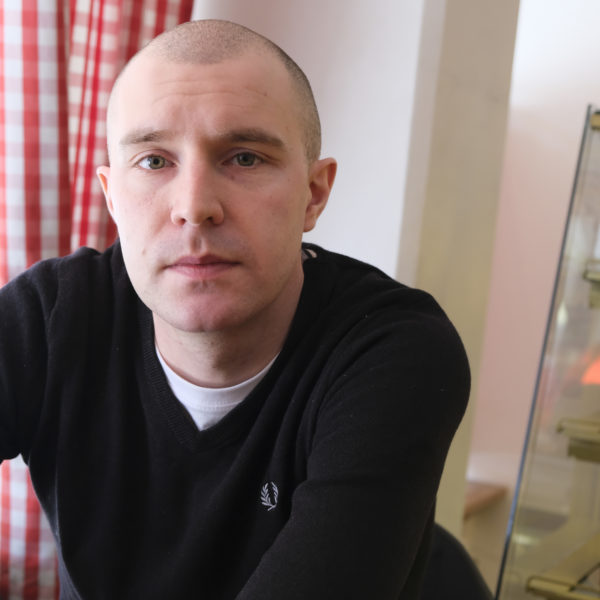 Elliot Baron sitter vid ett bort på ett konditori. Ett fönster med rödvitrutig gardin syns i bakgrunden.