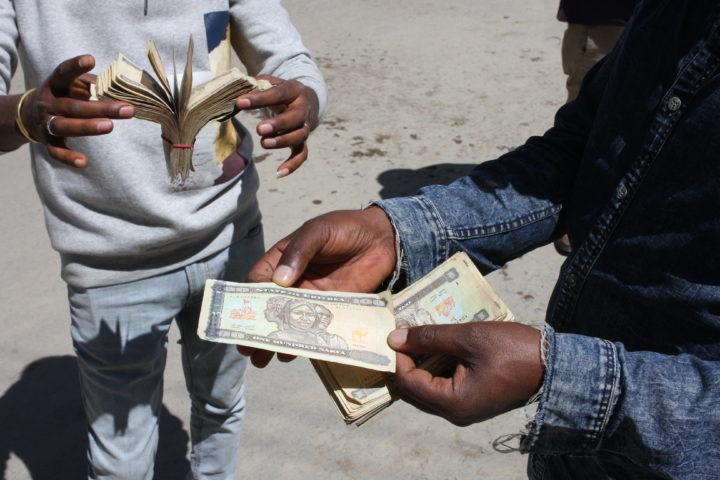 Två par händer håller i sedlar.