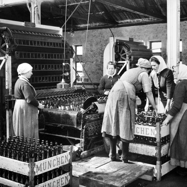 Bryggeriarbeterskor fyller backar med flaskor.