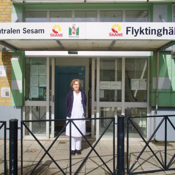Åsa Wieslander, sjuksköterska på Flyktinghälsan, i vita arbetskläder framför Flyktinghälsans entré.