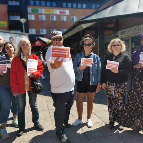 """Bild på personer som demonstrerar mot marknadshyror. De håller i röda skyltar där det står """"nej till marknadshyror"""""""