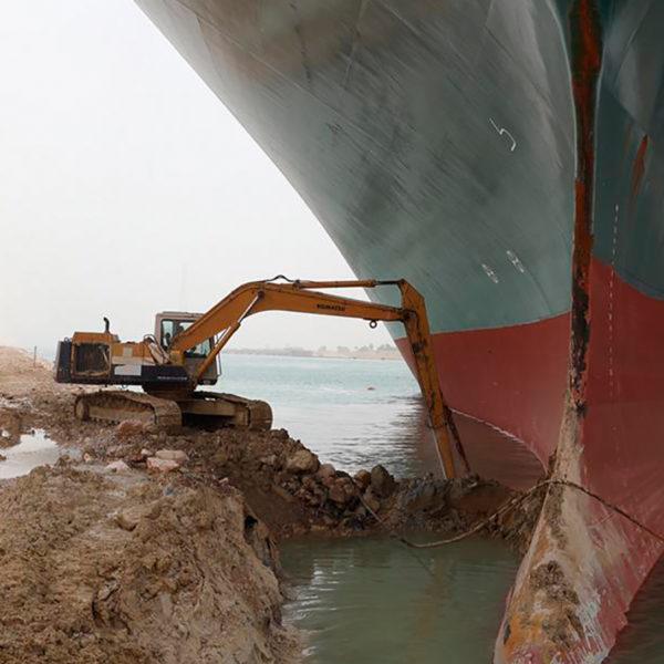 Liten grävmaskin kämpar för att få loss stort fartyg.