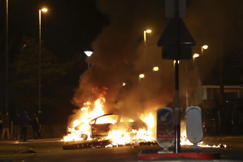 Bil i brand, under gatlyktorna i ett kvällsmörkt Londonderry.