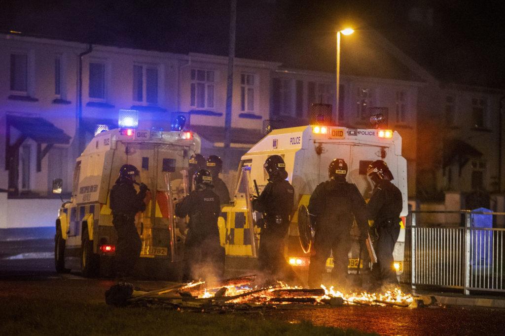 Kravallklädda poliser på en kvällsmörk gata. På markan ligger brinnande plankor.
