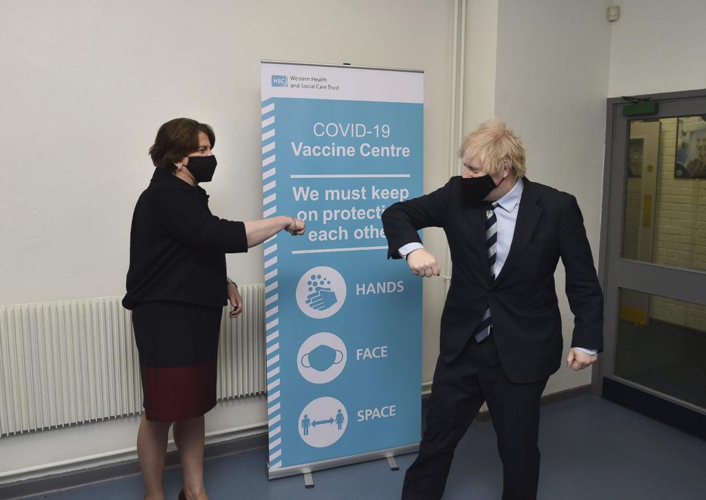 Storbritanniens premiärminsiter Boris Johnson och DUP:s partiledare Arlene Foster coronahälsar på varandra med armbågen under ett besökt på ett vaccinationscenter i Enniskillen