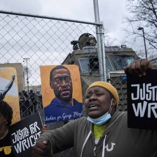 Kvinna håller upp plakat efter poliens mord Daunte Wright i Minneapolis