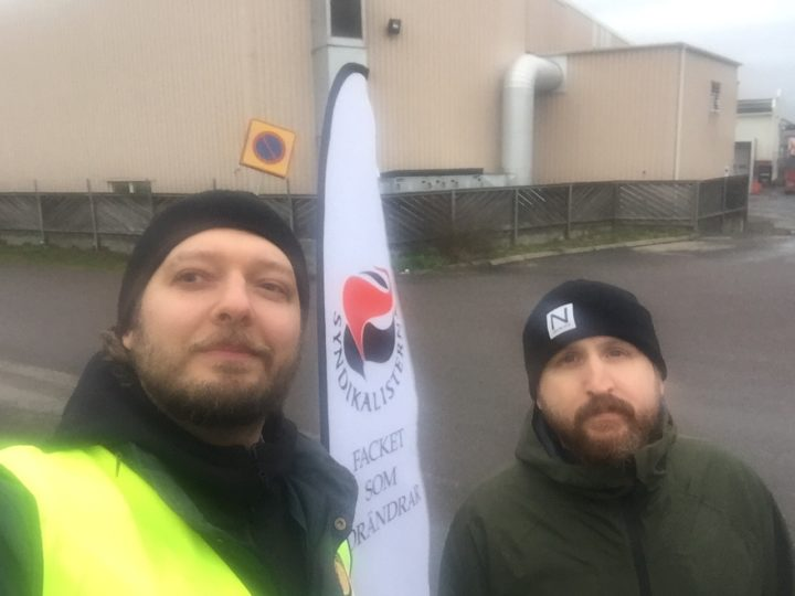 Emil Broberg och Per Hagander framför en SAC-flagga.