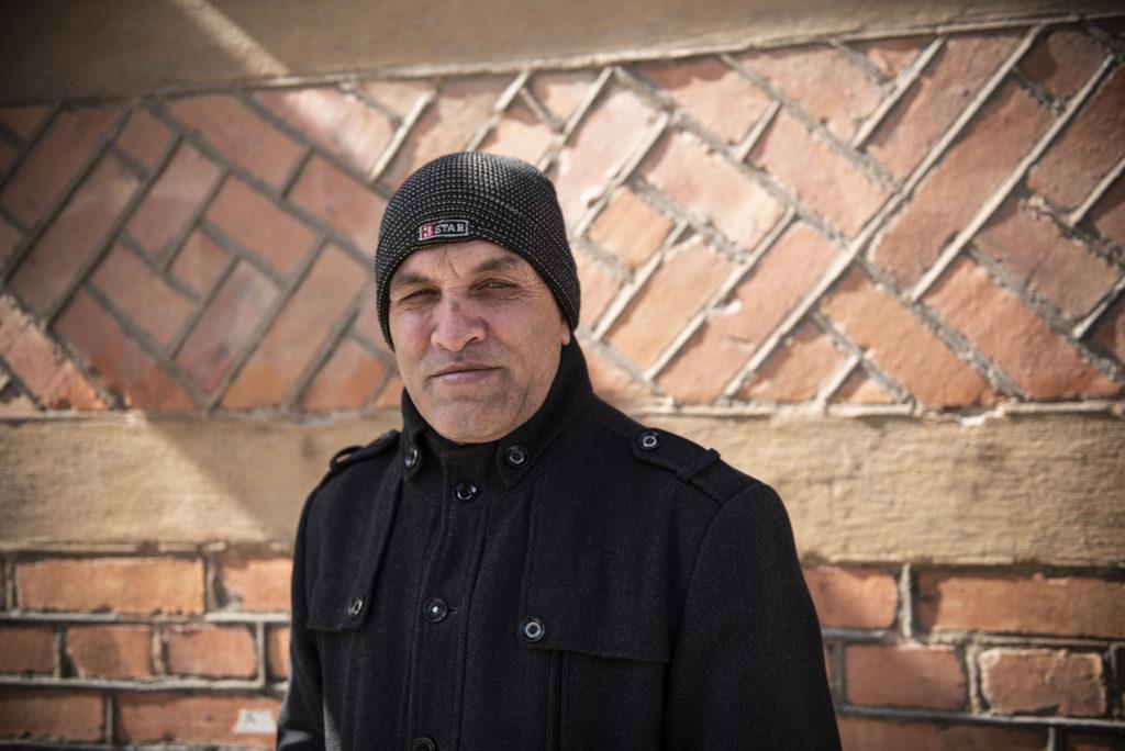 Khalid Hussein framför en tegelvägg.