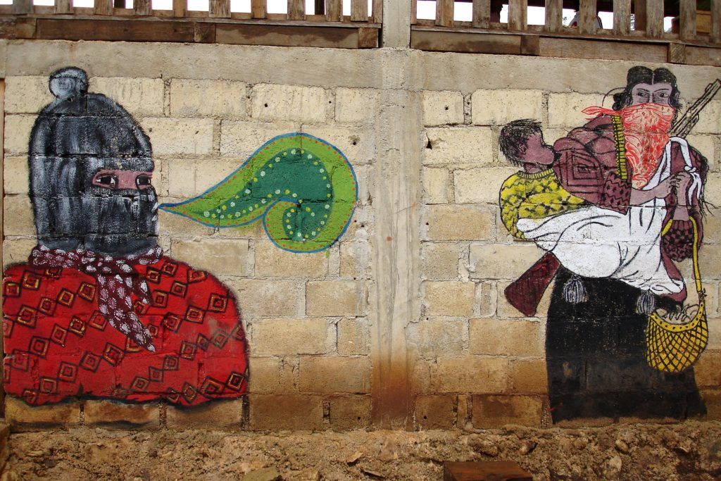 Väggmålning av en maskerad person och en kvinna med gevär och ett barn i sjal på ryggen.