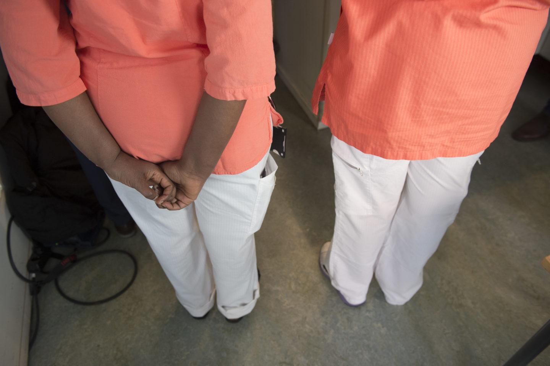 Två undersköterskor i arbetskläder fotograferade bakifrån.