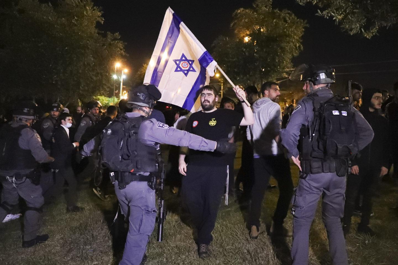 Högerextrem demonstrant i Jerusalem som viftar med israelisk flagga framför polis