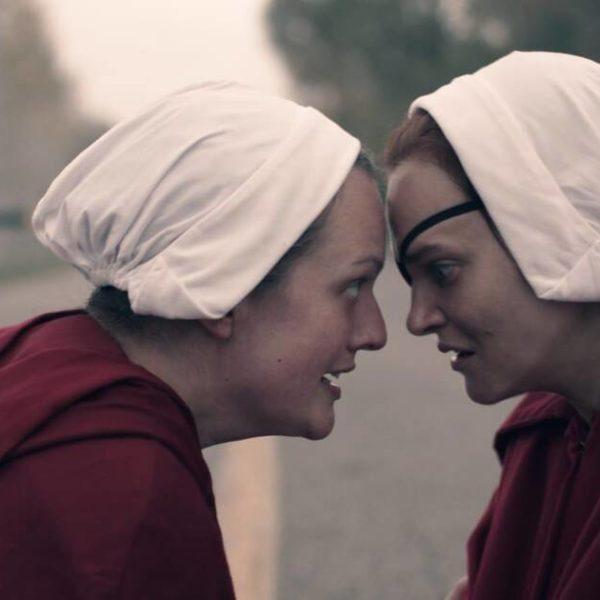 June och Janine med pannorna mot varandra. Klädda i röda caper och vita hättor.