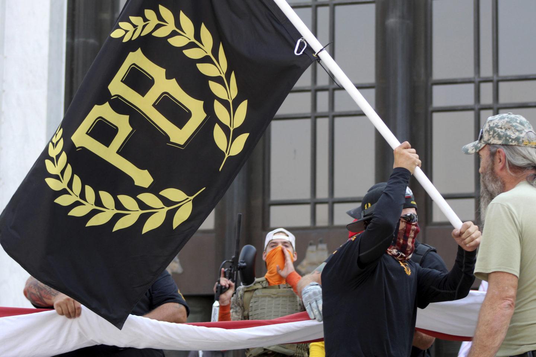En medlem i högerradikala Proud boys viftar med en svart flagga med bokstäverna PB på framför Oregons parlamentsbyggnad.