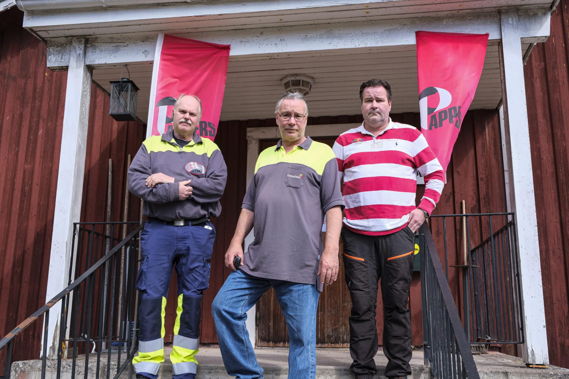Göran Israelsson, Patrik Aronsson och Anders Pettersson utanför Pappersavdelningens rödmålade hus på Kvarnsvedens pappersbruk. De står på trappan. Bakom dem hänger två vimplar med Pappers logga på.